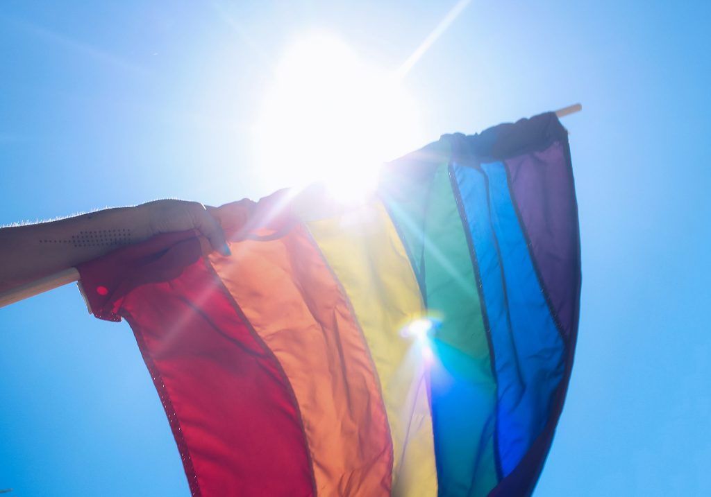 An image of an LGBT+ Pride Flag being held in a person's hand.