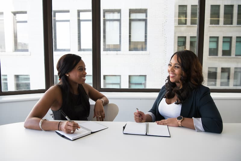 Two black women discussing business in the office