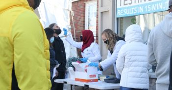 Medical professionals administer rapid tests at an outdoor testing location.