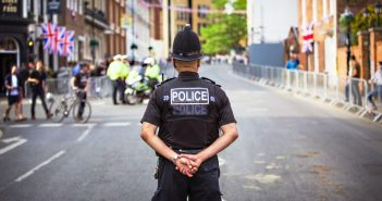 A picture of a police officer standing in a street.