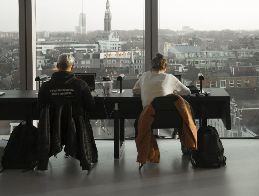 Students study with a view looking out across the city.